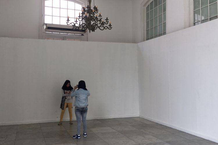 Pengunjung berfoto di spot berlatar putih yang ada di pintu masuk Gedung A Galeri Nasional Indonesia, Jakarta, Kamis (11/1/2018).
