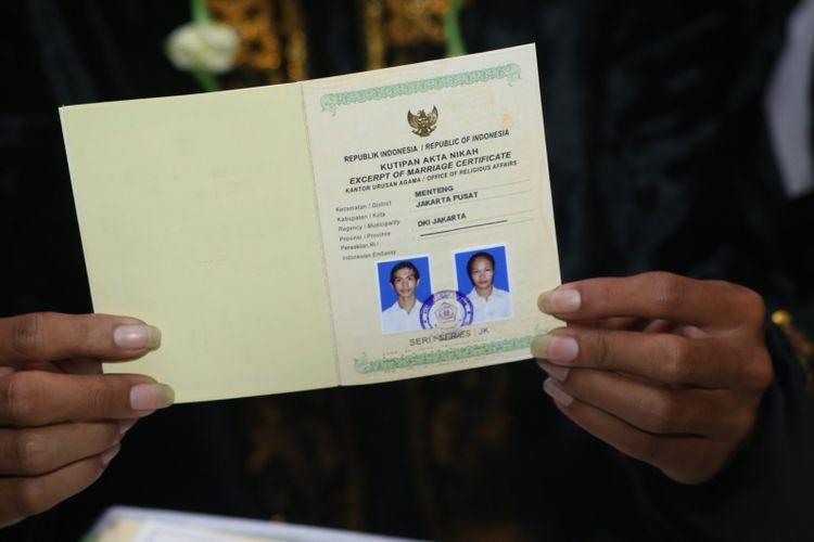 Sepasang pengantin menunjukkan buku nikahnya usai mengikuti nikah massal di jalan MH Thamrin, Jakarta Pusat, Minggu (31/12/2017). Nikah massal yang diadakan oleh pemerintah DKI Jakarta ini diikuti sebanyak 437 pasangan pengantin dari berbagai usia.