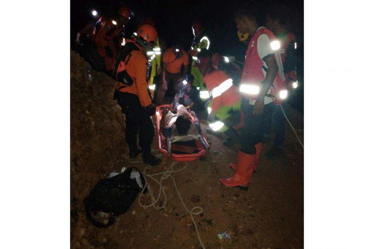 Sejumlah anggota tim SAR mengevakuasi salah seorang korban penambang emas yang tertimbun longsor di Desa Bakan, Kecamatan Lolayan, Kabupaten Bolaang Mongondow, Sulawesi Utara, Selasa (26/2/2019) malam. Sekitar 60 pekerja tertimbun longsor di lokasi penambangan emas tanpa izin tersebut.