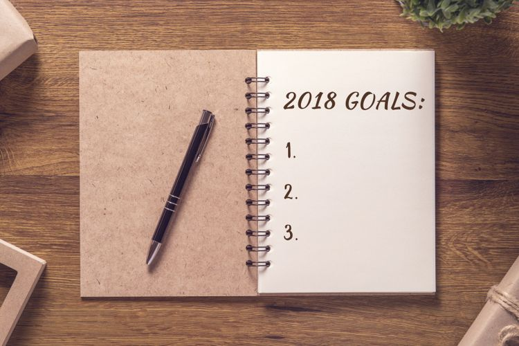 2018 goals list in notebook with gift box new year on wooden table background.