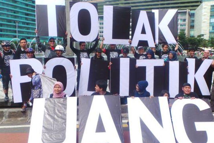 Aktivis Antikorupsi membentangkan papan bertuliskan Tolak Politik Uang di Bundaran Hotel Indonesia (HI), Jakarta, Minggu (23/2/2014).