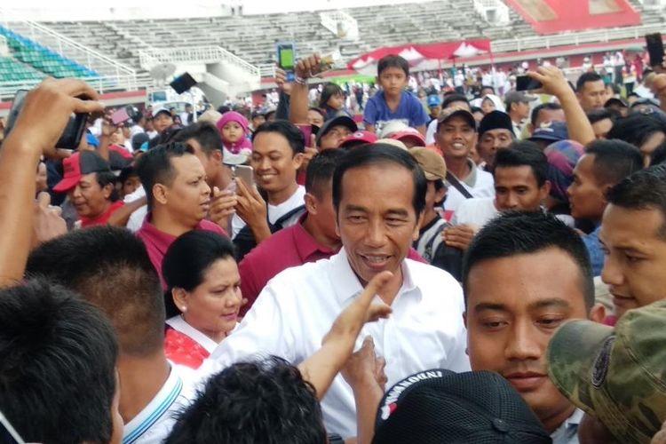 Calon presiden nomor urut 01 Joko Widodo (Jokowi) disambut pendukungnya saat tiba di Stadion Jember Sport Garden (JSG) di Desa Ajung, Kecamatan Ajung, Kabupaten Jember, Jawa Timur, Senin (25/3/2019).