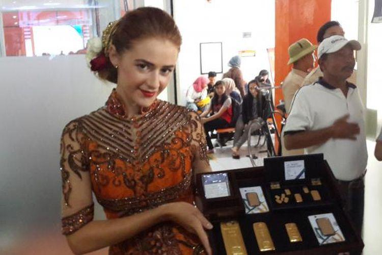 Seorang model saat menampilkan model emas batangan dalam grand launching kerja sama antara PT Pos Indonesia dan PT Antam di Kantor Pos Malang, Senin (6/2/2017)