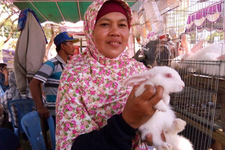 Hernanik, warga Desa Kinandang, Kabupaten Magetan, Jawa Timur, sembari memegang kelinci new zealand white, berbalik arah memelihara kelinci pedaging dari awalnya kelinci peliharaan sejak 2015.