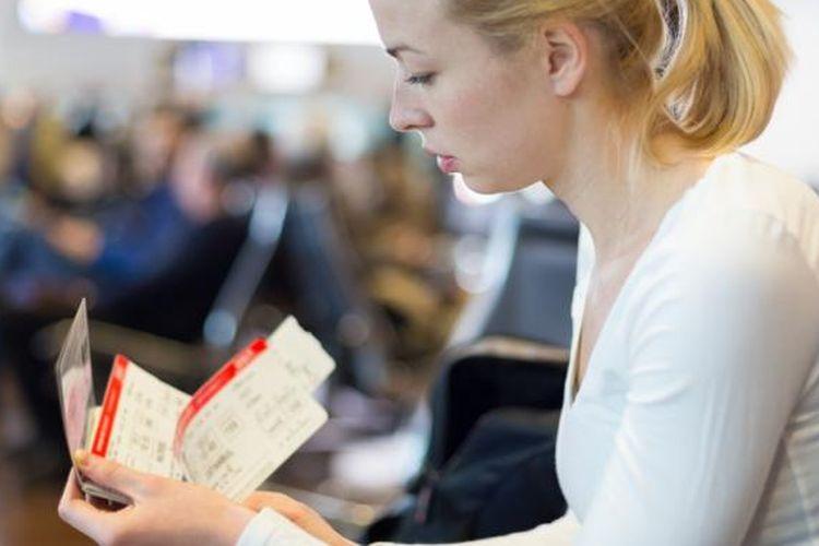 Penumpang pesawat memegang boarding pass.
