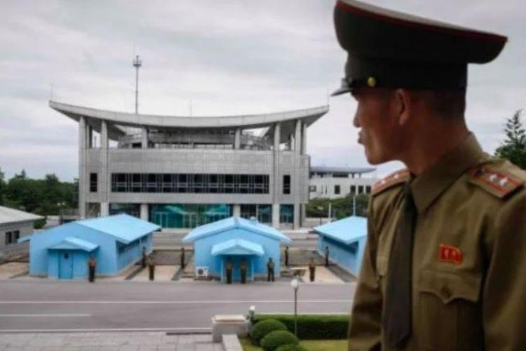 Anggota Tentara Rakyat Korea berdiri di sisi Korea Utara dan menghadap ke wilayah Korea Selatan di desa perbatasan, Panmunjom.