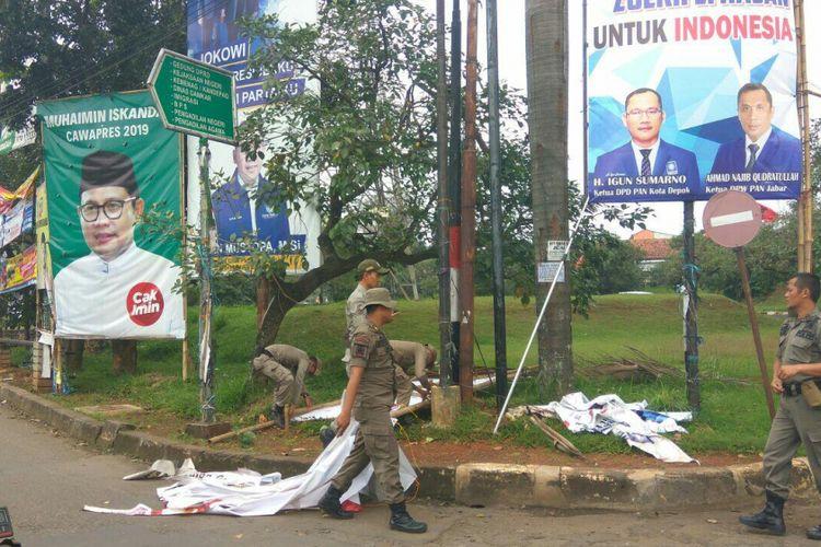 Satpol PP membongkar alat peraga kampanye yang terdapat di Jalan Boulevard Grand Depok City, Rabu (14/2/2018).