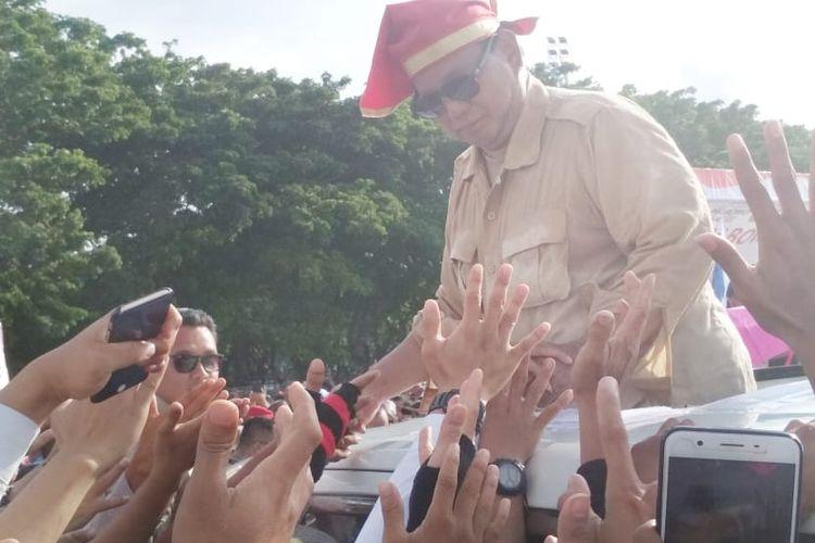 Capres nomor urut 02 Prabowo Subianto menyalami para pendukungnya saat hendak keluar dari Lapangan Karebosi, Makassar, Sulawesi Selatan, usai berorasi dalam kampanye akbar, Minggu (24/3/2019).