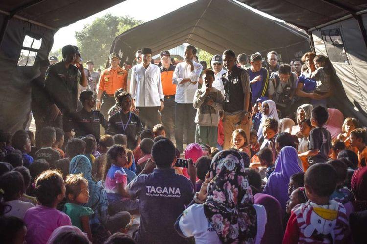 Presiden Joko Widodo (tengah) didampingi Gubernur NTB TGB Zainul Majdi (kedua kiri) berdialog dengan anak-anak korban gempa di Desa Madayin, Kecamatan Sambelia, Selong, Lombok Timur, NTB, Senin (30/7/2018). Presiden Jokowi mengatakan pemerintah akan memberikan bantuan untuk perbaikan Rp 50 juta per rumah korban gempa yang mengalami kerusakan.