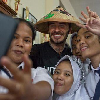 Duta Kehormatan UNICEF David Beckham berfoto bersama Sripun (15) dan para siswa di SMPN 17 di Semarang, Jawa Tengah, Indonesia, 27 Maret 2018. Sripun diunjuk oleh lingkungannya untuk menjadi agen perubahan dan berpartisipasi dalam program anti-bullying yang diinisiasi UNICEF.