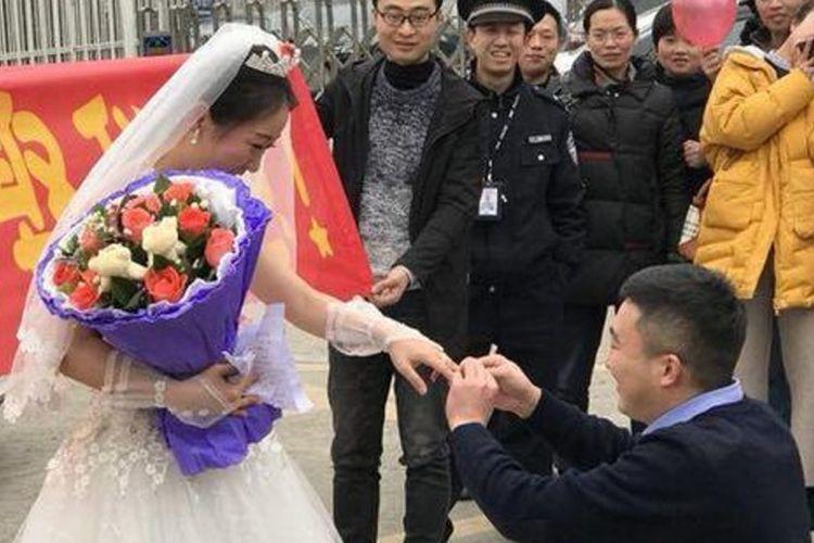 Zhao Wanping bersimpuh dan memakaikan cincin ke jari kekasihnya, Yuan Mingyu setelah dilamar di depan penjara tempat dia bekerja di Dazhou.