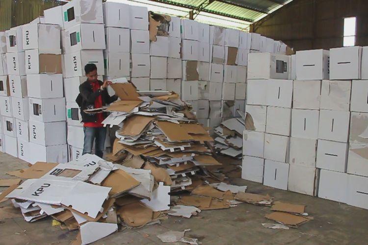 Seorang warga sedang melihat tumpukan kardus kotak surat suara yang rusak di dalam gudang logistik KPU di Kecamatan Plumbon, Kabupaten Cirebon, Jawa Barat, Selasa (12/2/2019).