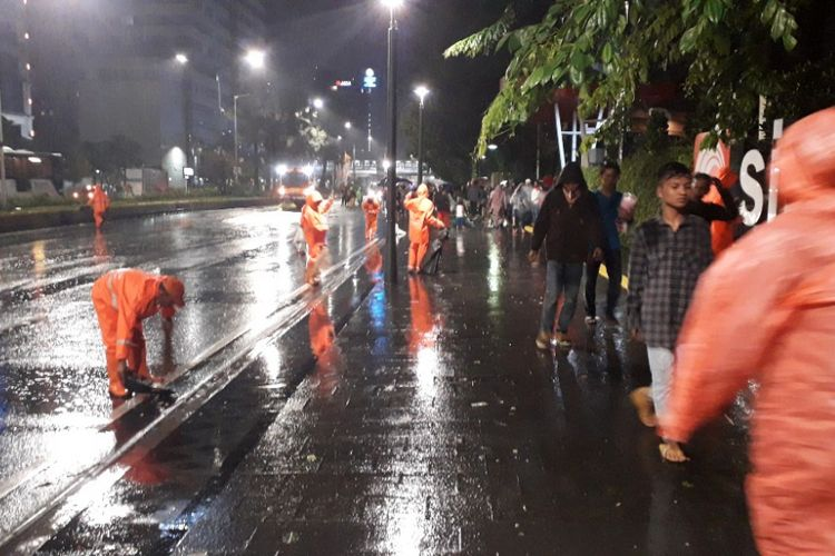 Pasukan Oranye mulai membersihkan sampah yang berserakan di Jalan MH Thamrin, Selasa (1/1/2019).