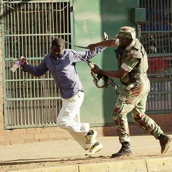 Seorang tentara Zimbabwe memukul pendukung oposisi di jalanan Harare Rabu (1/8/2018). Bentrokan terjadi antara pendukung oposisi dan pasukan setelah massa menyebut Pemilihan Umum di Zimbabwe telah dicurangi.