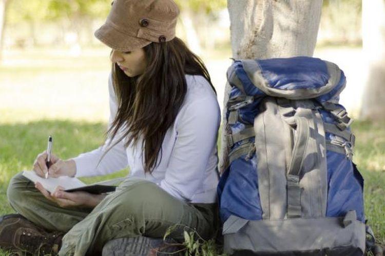ILUSTRASI - Pelancong mencatat perjalanannya di jurnal.