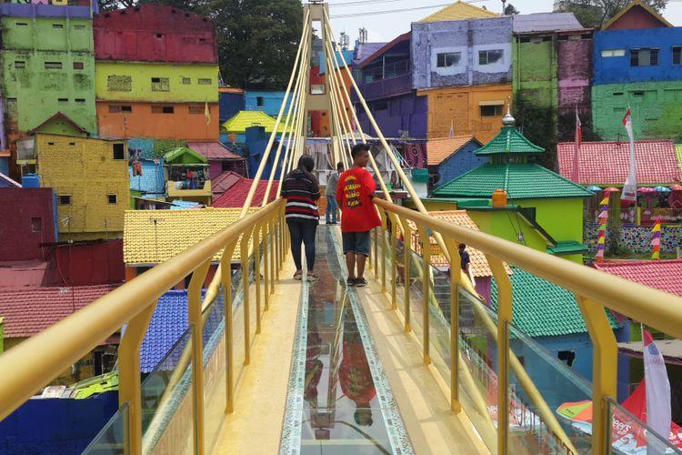Sejumlah wisatawan saat melintas di jembatan kaca yang menghubungkan Kampung Warna - warni dan Kampung Tridi di Kota Malang, Jawa Timur, Selasa (10/10/2017)