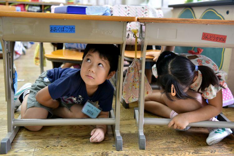 Anak-anak sekolah dasar berlindung di bawah meja mereka saat latihan gempa di sebuah sekolah di Tokyo pada tanggal 1 September 2015. Latihan anti-bencana nasional diadakan pada tanggal 1 September pada hari peringatan gempa besar 1923 yang menewaskan lebih dari 100.000 orang di daerah metropolitan Tokyo.