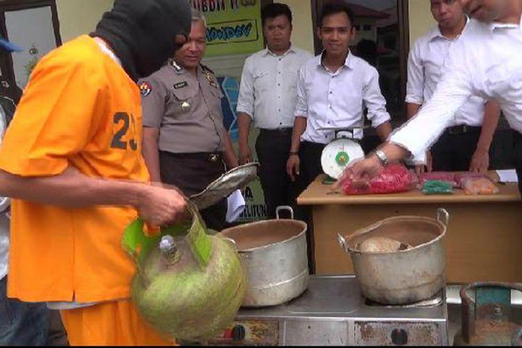 Pelaku yang diringkus Polda Kepulauan Bangka Belitung, memeragakan tabung gas subsidi yang dipanaskan untuk tujuan pengoplosan