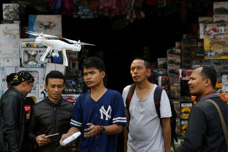 Pedagang memperlihatkan cara operasional drone mainan kepada pembeli di pasar mainan Gembrong, Jakarta, Jumat (27/7/2018). Mainan impor dari Tiongkok merupakan salah satu barang yang kini membanjiri pasar di dalam negeri.  KOMPAS/PRIYOMBODO (PRI) 27-07-2018  untuk tematik ekonomi senin (30/7/2018).