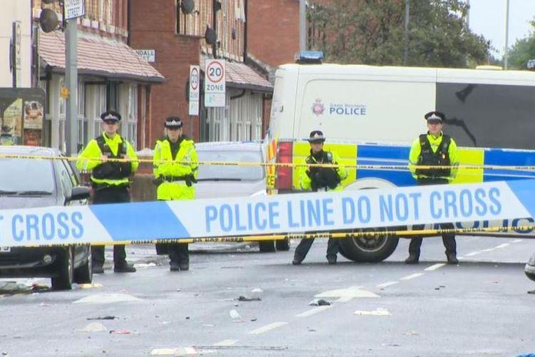 Petugas kepolisian Manchester berjaga di dalam garis polisi yang dipasang di Claremont Road, Moss Side, Manchester, Inggris, usai terjadinya insiden penembakan yang melukai 10 orang, Sabtu (11/8/2018).