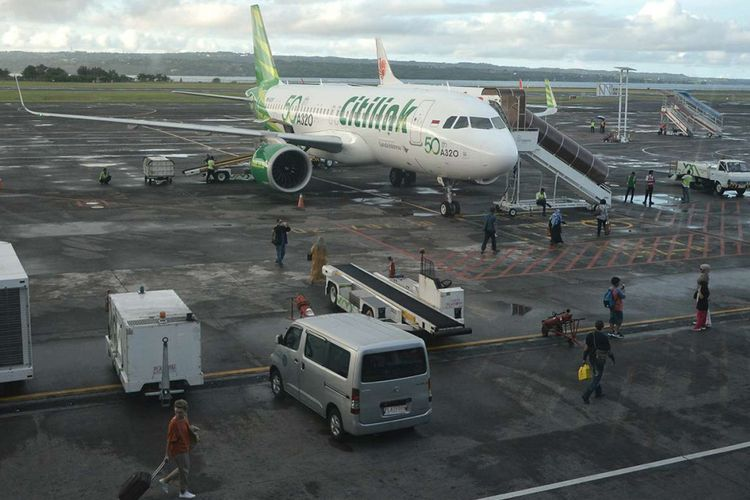 Penumpang bersiap menaiki pesawat udara di Bandara Internasional I Gusti Ngurah Rai, Bali, Rabu (13/12/2017). Aktivitas penerbangan di Bandara I Gusti Ngurah Rai terpantau normal meskipun Gunung Agung terus mengembuskan asap dengan ketinggian hingga 2.000 meter.