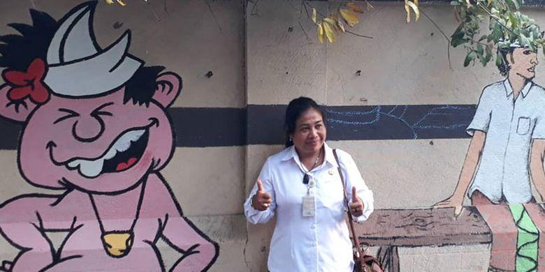 Lurah Sesetan, Ketut Sri Karyawati dengan latar belakang seni mural di tembok dinding sepanjang Sungai Rangda di Banjar Suwung Batan Kendal, Sesetan, Denpasar, Bali.