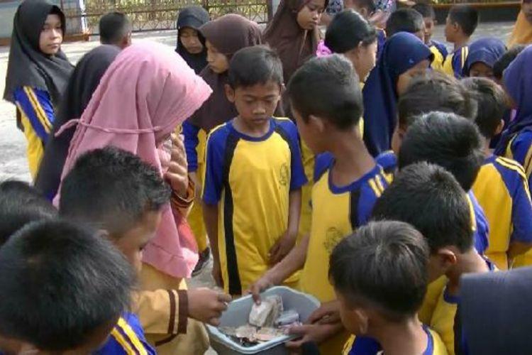 Siswa SD Mentel 1, Kecamatan Tanjungsari, Gunungkidul, mengumpulkan uang saku untuk membantu memberikan honor guru, Jumat (14/9/2018).
