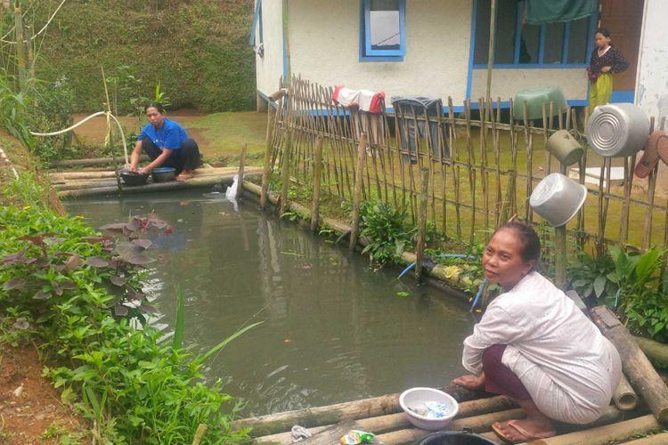 Dua warga mencuci di atas kolam yang airnya bersumber dari selokan di Kampung Pasir Tengah, Desa Gede Pangrango, kadudampit, Sukabumi, Jawa Barat, Rabu (13/6/2018).