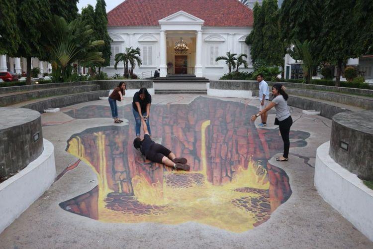 Pengunjung berfoto di spot gambar tiga dimensi yang ada di Galeri Nasional Indonesia, Jakarta, Kamis (11/1/2018).