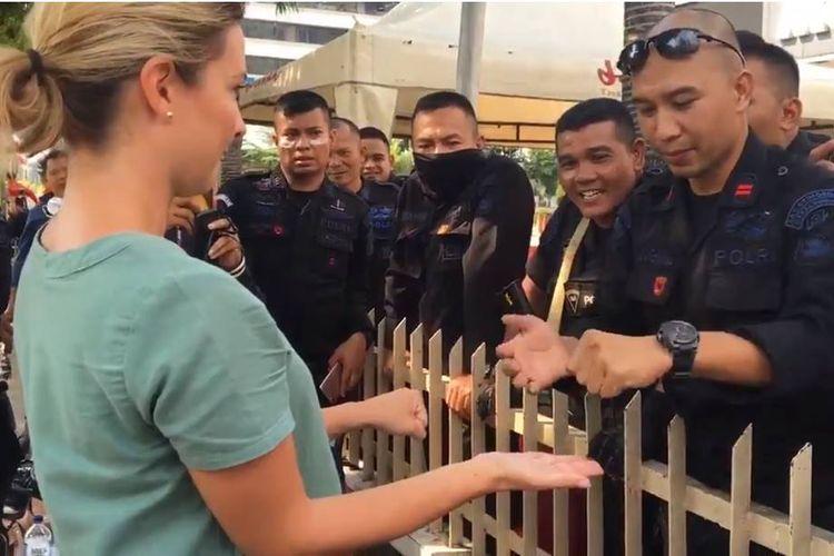 Ridho Vernando, anggota Brimob berpangkat Bharatu asal Padang, Sumatera Barat, (kanan) sedang menunjukkan kelihaiannya dalam sulap di depan jurnalis asal Australia, Renea Henry. Aksi menghibur ini dilakukannya di sela bertugas pada aksi 22 Mei di Jakarta.