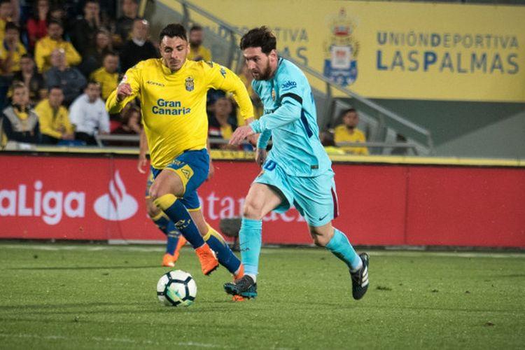 Striker utama Barcelona, Lionel Messi, mendapat pengawalan ketat dari pemain tuan rumah Las Palmas, Ximo Navarro Jimenez, dalam laga lanjutan Liga Spanyol di Stadion Gran Canaria, Kamis (1/3/2018).