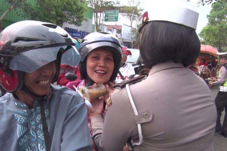 Salah satu polisi wanita mengancingkan tali helm pengaman pengendara,sambil membagikan takjil berbuka puasa (31/05/2017)
