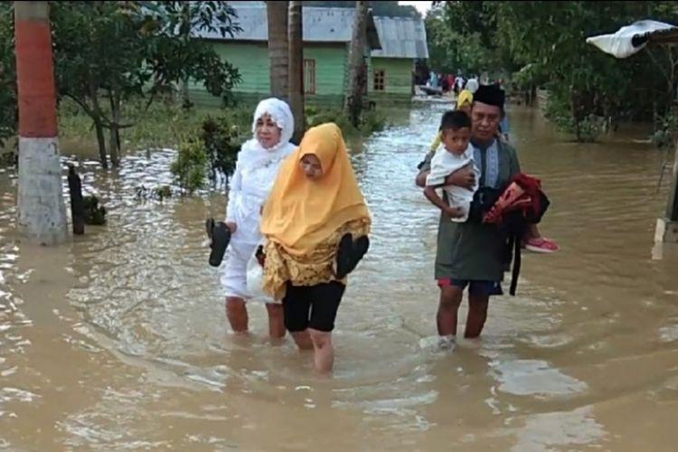 Warga korban banjir di Kota Kendari, Sulawesi Tenggara, harus melewati genangan banjir untuk menuju lokasi shalat Id, Rabu (5/6/2019).