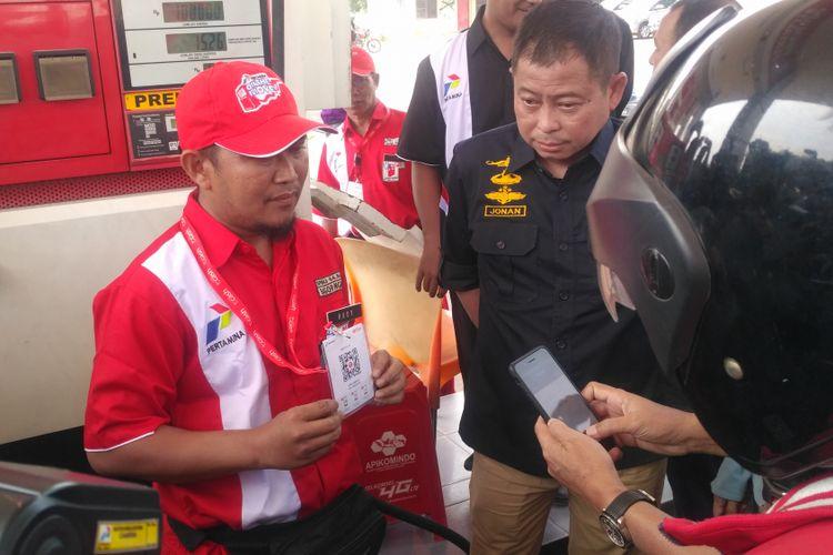 Direktur Pemasaran Retail Pertamina Mas'ud Khamid didampingi Menteri ESDM Ignasius Jonan memperagakan penggunaan T-Cash sebagai alat pembayaran BBM di SPBU wilayah Kertosono, Jawa Timur, Minggu (3/6/2018).