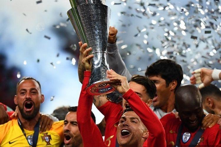 Kapten Portugal Cristiano Ronaldo mengangkat trofi saat ia merayakan gelar juara dengan rekan setimnya setelah pertandingan final UEFA Nations League antara Portugal vs Belanda di Stadion Dragao di Porto pada 9 Juni 2019.