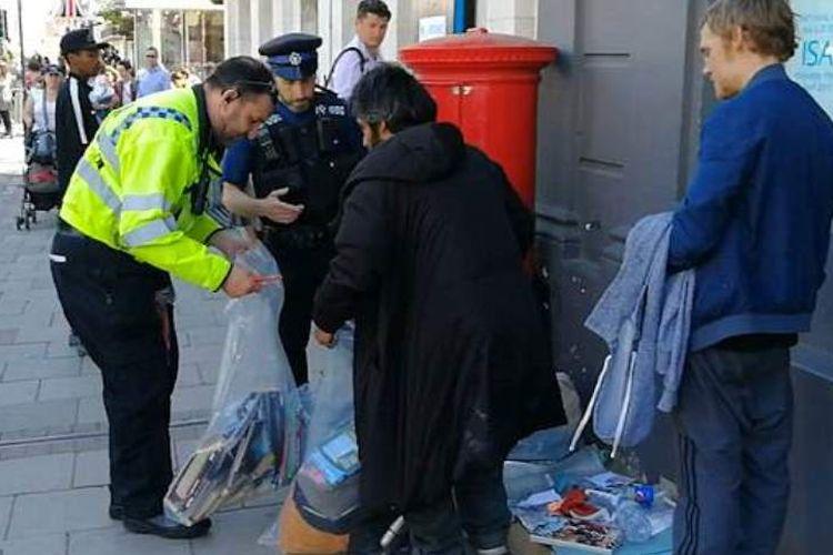 Petugas polisi membantu seorang tunawisma mengemasi barang-barang mereka menjelang dilangsungkannya pernikahan akbar keluarga kerajaan antara Pangeran Harry dengan Meghan Markle.