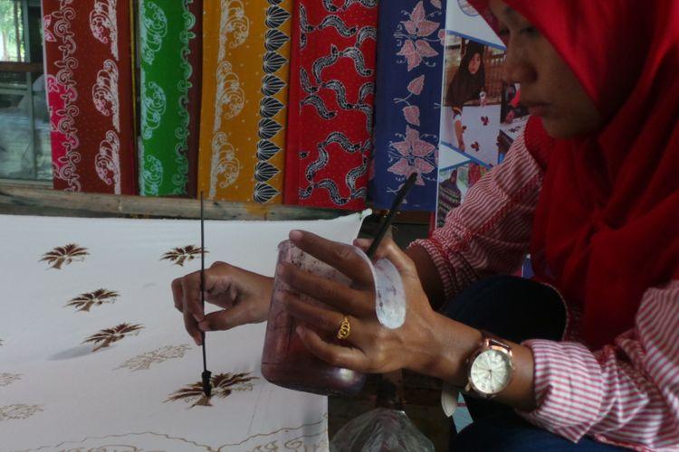 Seorang pembuat batik Riau bernama Ade sedang membuat batik motif sawit. Ade adalah salah satu pegawai yang dilatih dan bekerja di Rumah Batik Andalan.