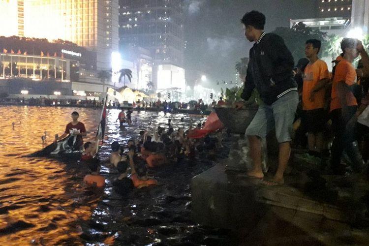 Sejumlah suporter Persija Jakarta menceburkan diri ke kolam Bundaran Hotel Indonesia, Mingu (9/12/2018).