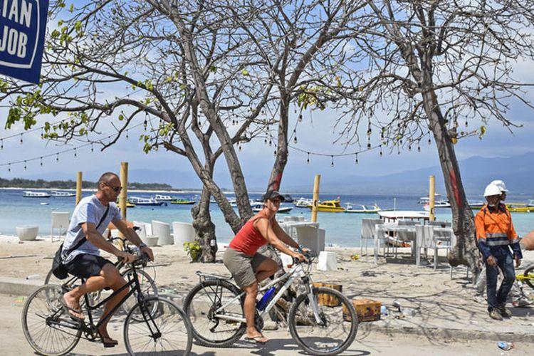Dua orang wisatawan asing mengendarai sepeda di kawasan wisata Gili Trawangan, Desa Gili Indah, Kecamatan Pemenang, Tanjung, Lombok Utara, NTB, Rabu (8/8/2018). Foto: Antara Foto/Ahmad Subaidi
