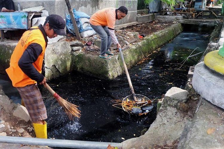 Pekerja Penanganan Prasarana dan Sarana Umum (PPSU) mengumpulkan sampah dari saluran air di Kelurahan Rawa Badak Utara, Jakarta Utara, Senin (26/6). Setiap kelurahan tetap menugaskan pekerja PPSU bekerja pada hari libur. Penerapan sistem piket ini berbeda di tiap kelurahan