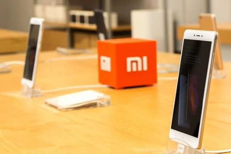 Ilustrasi logo Xiaomi di antara dua ponsel Redmi