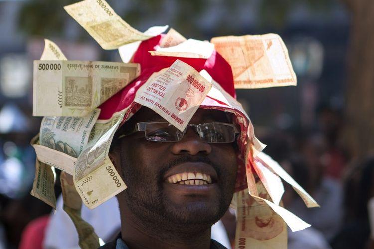Pria Zimbabwe mengenakan topi yang dihiasi lembaran uang dollar Zimbabwe yang tidak lagi bernilai akibat hiperinflasi.