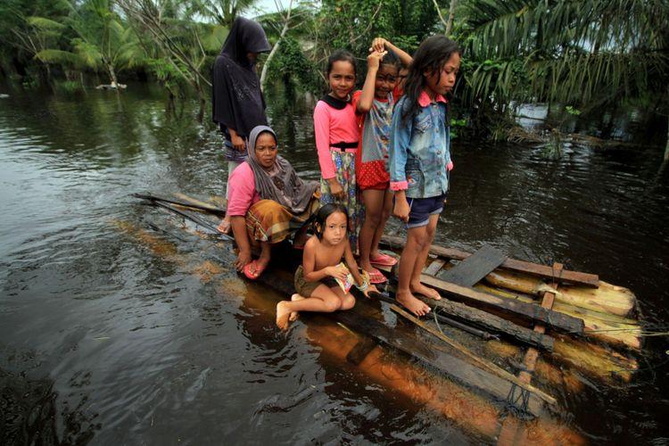 Warga yang terisolir akibat banjir menggunakan rakit pisang di Desa Cot U Sibak, Kecamatan Lhoksukon, Aceh Utara, Aceh, Kamis (7/12/2017). Sebanyak 8000 jiwa lebih korban banjir delapan kecamatan bagian pedalaman pantai Timur Aceh Utara yang masih terisolir banjir besar mulai keluar menyelamatkan keluarga dan barang berharga, karena mereka kehabisan makanan dan air bersih.