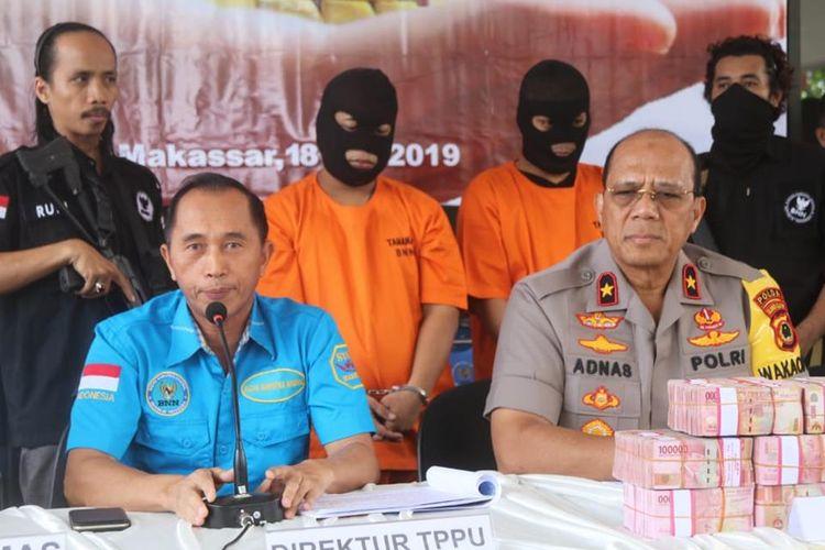 Dua pelaku peredaran narkoba (bertopeng) yang melakukan tindak pidana pencucian uang (TPPU) untuk menyamarkan kekayaannya dari hasil penjualan narkoba saat dirilis BNN di Makassar, Kamis (18/9/2019).