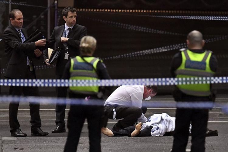 Seorang polisi memeriksa korban tewas dalam insiden penikaman di kota Melbourne, Australia pada Jumat (9/11/2018).