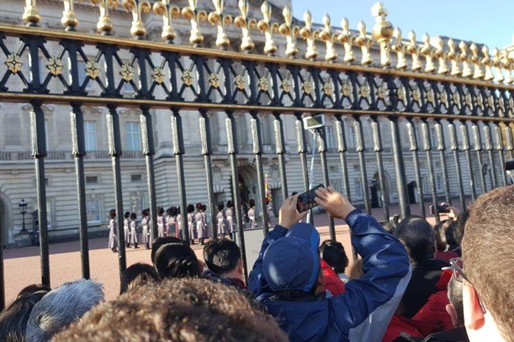 Pengunjung memadari sepanjang pagar Buckingham Palace untuk menyaksikan upacara changing of the guard, upacara pergantian pasukan pengawal di Buckingham Palace, kediaman resmi Ratu Inggris, Queen Elisabeth II, Senin (6/11/2017). Upacara pergantian biasanya berlangsung setiap hari Senin, Rabu, Jumat dan Minggu, sekitar pukul 11.00 WIB.