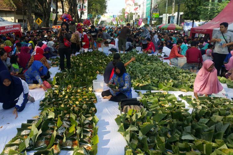 Ribuan pincuk nasi pecel yang disajikan Pemkot Madiun memecahkan rekor MURI hingga rekor dunia memperingati satu abad kota itu dii Jalan Pahlawan Kota Madiun, Jumat (22/6/2018). (KOMPAS.com/Muhlis Al Alawi)