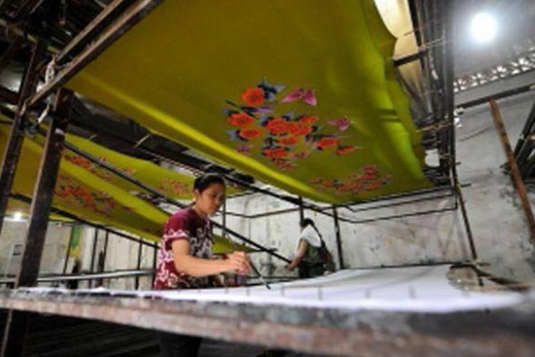 Pekerja menyelesaikan pembuatan kain batik yang khusus di ekspor ke Malaysia di Kampung Batik Laweyan, Solo, Jawa Tengah, Kamis (4/7/2013).