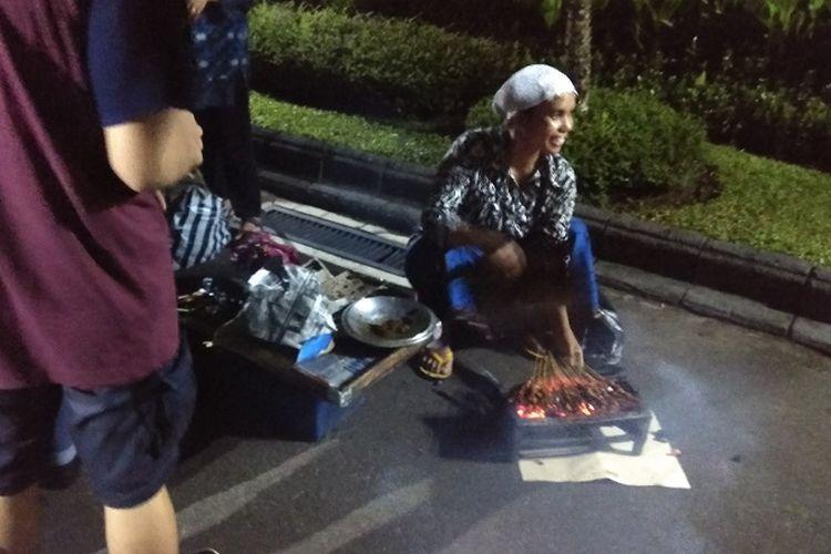 Penjual sate ayam di sekitar Kawasan Malioboro, Khotimah (25) menyiapkan sate ayam untuk pengunjung Gedung Agung Istana Kepresidenan, Yogyakarta, Minggu (31/12/2017). Pada malam tahun baru 2018, beberapa pedagang dan pengunjung Malioboro diajak masuk oleh Presiden Joko Widodo.