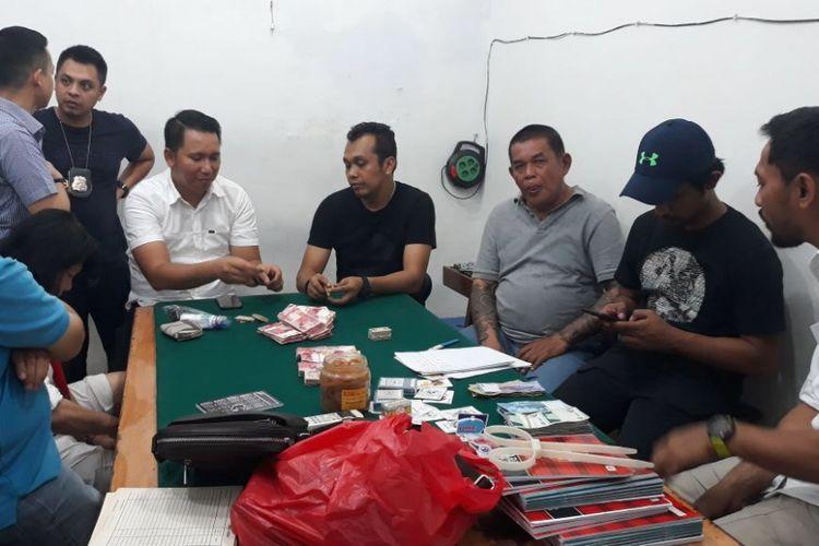 Polisi menggerebek dua rumah judi di Jalan Dwi Warna 8, Gang C Nomor 42, Sawah Besar, Jakarta Pusat, Senin (12/3/2018) malam. 87 penjudi diamankan dia dua rumah tersebut